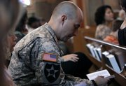 A soldier reads a Bible during Sunday church service at the 1st Air Cavalry Division Memorial Chapel at Fort Hood, Texas.