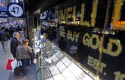 Shoppers browse store windows Wednesday on 47th Street in New York's diamond district, where gold is bought and sold. The price of gold set a new record Wednesday of $1,119 an ounce.