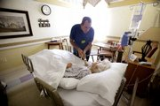 Joe Takach, in this Oct. 30 photo, talks to his friend Lillian Landry as she spends her last days in the hospice wing of an Oakland Park, Fla., hospital. She made her end-of-life decisions on how she wanted to die and to be buried.  Democrats in the U.S. House are trying to nudge more Americans to make their end-of-life decisions.