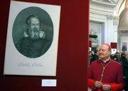 "Monsignor Gianfranco Ravasi looks on near a portrait of Italian astronomer Galileo Galilei, part of the ""Galilei Divin Uomo"" (Galilei Divine Man) exhibit, in the Santa Maria degli Angeli Basilica in Rome in this Feb. 15, 2009, file photo."