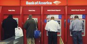 Customers use ATMs at a Bank of America branch office in Boston in this Oct. 16 file photo. The Federal Reserve has issued a new rule that will prohibit banks from charging overdraft fees on ATM and debit card transactions unless a customer allows it. The new rule will take effect July 1.