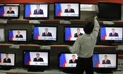 A vendor adjusts a display with TV sets broadcasting Russian President Dmitry Medvedev's address to the nation at a Moscow shop on Thursday. In his speech, Medvedev suggested condensing the number of time zones across the 5,500-mile wide country from 11 to four.