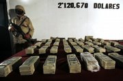A soldier stands guard next to more than $2 million in seized U.S. currency during a presentation to the press in Tijuana, Mexico, late Thursday. Authorities say they seized the money and some weapons in Tijuana early Thursday after responding to an anonymous citizen tip. Mexicans are raising objections to Forbes magazine ranking their most-wanted drug lord in its list of 'powerful' people.