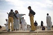 "Displaced Pakistani tribal people, who fled the tribal area of Waziristan along the Afghanistan border after fighting between security forces and militants, are checked Friday by security personal prior to receiving relief supplies in Dera Ismail Khan, Pakistan. Militants are increasingly turning against the Pakistani government that once nurtured them, creating what the information minister for North West Frontier Province calls ""a guerrilla war."""