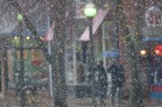 The first snowfall of the year dropped some large and blowing flakes on Lawrence around noon Monday, creating an impressionistic view of two shoppers downtown.