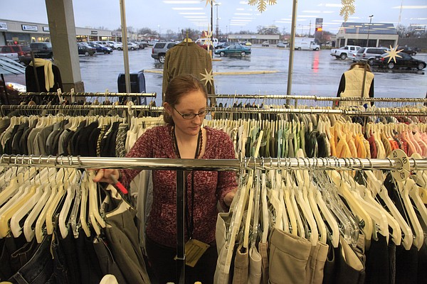 Kasey Lane, a worker at Lasting Impressions in The Malls Shopping Center, sorts through clothes for sale Tuesday, Nov. 17, 2009.