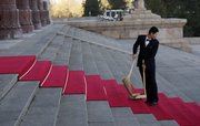 A Chinese staff member looks back as he sweeps a red carpet laid out for U.S. President Barack Obama's arrival today at the Great Hall of the People in Beijing.