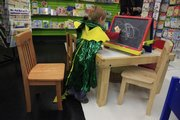 Jake Dudley, 4, Lawrence, plays with a chalkboard at The Toy Store, 936 Mass. He's wearing a dragon/knight reversible cape and hood by Creative Education of Canada.