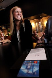Anne Miller, Kansas University student, finishes her glass of sparkling wine and prepares to pay her check at 715 in downtown Lawrence. Servers at 715 say they try to not rush people out of the restaurant by dropping the check too soon.