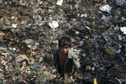 Vijay, a street child, stands on a pile of garbage Wednesday in Dharavi, Asia's largest slum, in Mumbai, India. Twenty years after the U.N. adopted a treaty guaranteeing children's rights, fewer youngsters are dying and more are going to school, but an estimated 1 billion still lack services essential to their survival and development, UNICEF said Thursday.