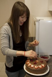 Nina Riley decorates the top of a chocolate frosting white cake with strawberries and pomegranate.  Riley and her roommate blog together their cooking recipes.