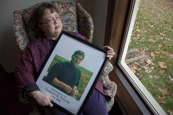 Rose Foster, of Lawrence, cradles a portrait of her late husband, Gordon Foster, who committed suicide at age 40. He had attempted suicide several times before and had been dealing with depression for years. At the time of his death, Rose had cancer and the family had just filed for bankruptcy.