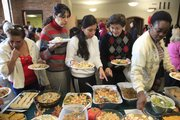 Women with Small World enjoy a holiday luncheon at First Presbyterian Church, 2415 Clinton Parkway. From left are Emita Cevaso, of Chile, Vanessa Aquilor, of Honduras, and Beygona Morgazavi, of Iran, sampling an array of dishes.