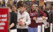 """Kristi Williams, of Hiawatha, manages a smile as she stands in the waiting line with Sherri Nelson, of Iola, second from left, at 7 a.m. Friday at Kohl's Department Store, 3240 Iowa. """"We've been going since midnight,"""" Nelson said. In front is Linda Jamison, of Ottawa."""