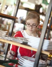 Molly Jones, Lawrence, looks through a selection of plates and glassware at Waxman Candles, 609 Mass.