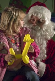 Santa listens to Liberty Justice-Dean, 5, give her ideas for Christmas.