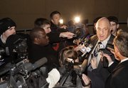 Kansas University athletic director Lew Perkins talks with media members outside the Anderson Family Football Complex on Thursday as he answers questions regarding the resignation of head coach Mark Mangino.