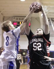 Lawrence High&#39;s Matthew Montes de Oca competes for a rebound with Washburn Rural&#39;s Ryan Roe during the second half, Friday, Dec. 4, 2009 at Washburn Rural High School in Topeka.
