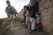 "United States Marine Cpl. Joseph Kelly of Va., from the 2nd MEB, 4th Light Armored Reconnaissance Battalion, walks past Afghan youths during a patrol Friday near Khan Nashin in the volatile province of Helmand, southern Afghanistan. About 1,000 Marines and 150 Afghan troops were taking part in ""Operation Cobra's Anger"" in a bid to disrupt Taliban supply and communications lines Friday in the Now Zad Valley of Helmand province."