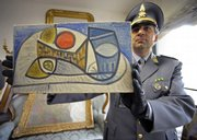 An Italian tax police officer holds a Picasso painting, one of the 19 masterpieces that were seized Saturday in Parma, Italy.