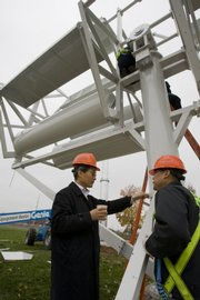 Designer Dr. Seungbae Lee, left, CEO of AeroNet, and his workers prepare to install the AES WindJet 5 Vertical Axis Twin-Rotor Wind Turbine behind A.L. Huber, a construction company, last month in Overland Park.