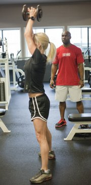 Lawrence Athletic Club          personal trainer Wayne Jackson, right, works with Tanya Dooley on dumbbell swings with 180-degree squat jumps at the center, 3201 Mesa Way.