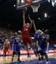 Kansas center Krysten Boogaard lays in a bucket over UMKC defenders Chazny Morris (33), Sam Sikkink (12) and Kim Nezianya (1) during the second half, Thursday, Dec. 10, 2009 at Allen Fieldhouse. At far left is Kansas guard Monica Engelman.