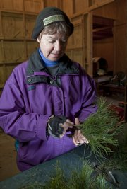 Kathy Heeb uses fresh-cut greenery to make wreaths and swags. Heeb runs Prairie Elf Christmas Trees in Lone Star, where wreaths and swags are made from Scotch and white pine branches.