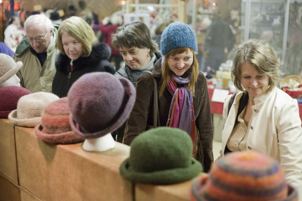 Erika Eden, second from right, and her mother Valerie Eden, right, both of Lawrence, look over hand-made soaps and hats with other shoppers at the Crane River Farm booth at the Holiday Farmers Market Saturday, Dec. 12, 2009. Large crowds filled the parking lot and the Knights of Columbus hall for the annual sale. In 2010, the market moved to the The Holiday Inn, 200 McDonald Drive.
