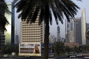A billboard of Sheik Mohammed Bin Rashid Al Maktoum, UAE Prime Minister and ruler of Dubai, is seen in front of Sheikh Zayed highway towers in this July 30 file photo in Dubai, United Arab Emirates. Dubai got a $10 billion lifeline from neighboring emirate Abu Dhabi to save one of its prized companies from imminent default Monday.