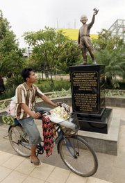 A coffee vendor on Tuesday rides past the statue of U.S. President Barack Obama as a 10-year-old boy at Menteng Park in Jakarta, Indonesia. The statue has been targeted in a Facebook campaign by thousands who say it should be removed.