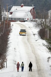 Women walk down a road Thursday in Vienna, Maine. The high cost of pavement has the town considering changing some of its 14 miles of paved roads back to gravel, which is cheaper to maintain.