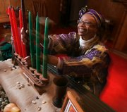 Ruth Ndiagne Dorsey sets up for Kwanzaa Dec. 8 at her church, The Shrine of the Black Madonna, in Atlanta. African-Americans' opinions of Kwanzaa vary, from saying it connects them to their ancestors to believing it racist.