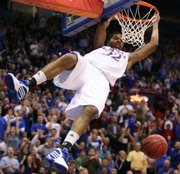 Kansas forward Marcus Morris swings on the rim after finishing a dunk against California during the first half, Tuesday, Dec. 22, 2009 at Allen Fieldhouse.