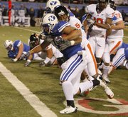 BYU running back Harvey Unga carries Oregon State safety Cameron Collins into the end zone for a touchdown in the Las Vegas Bowl. BYU won, 44-20, Tuesday in Las Vegas.