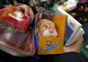 "A shopper waits in a checkout line with a Zhu Zhu Pet hamster and other items Nov. 27 at the Toys ""R"" Us in Camp Hill, Pa. Those who haven't gotten their hands on Zhu Zhu pets yet may have to wait until after Christmas."