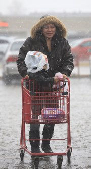 Clarissa Atkins, Lawrence, covers her daughter Jaila, 1, with a plastic shopping bag and pushes her groceries to her car in the Hillcrest Shopping Center trying to avoid the heavy rain. December's wacky weather made a lot of people do a double take on Wednesday morning as hail and heavy rain fell.