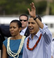 President Barack Obama and first lady Michelle Obama, both wearing leis, greet the crowd at Hickham Air Force Base Thursday in Honolulu.