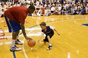 Kansas' Thomas Robinson dribbles around Jake Hendrickson, 8, Chanutte, Kan., during the WInter Clinic on Sunday, Dec. 27, 2009, at Allen Fieldhouse.