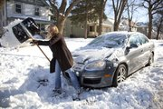 Lawrence resident Carrie Mayhew digs her car out on Monday as it was snowed in by city street crews outside her house in Old West Lawrence.