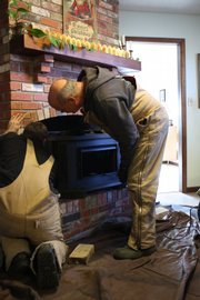 Workers from Swims & Sweeps install a high efficiency wood burning stove.
