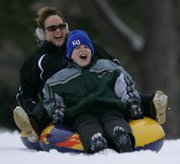 Lawrence resident Marissa Brumley and her son, K.J. Brumley, 11, cruise down Campanile Hill at Kansas University. The mother and son, like other area residents, experienced the fun side of the recent snowfall on Dec. 30, 2009.