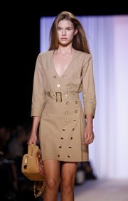 A model wears spring 2010 fashion by Tommy Hilfiger during Fashion Week in New York. Her dress features two trends for spring: khaki and military-style details.
