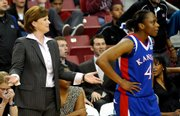 KU coach Bonnie Henrickson, left, questions a foul call against Danielle McCray, right.
