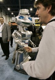 Aan attendee shakes hands with Hoovers Mobile's remote-controlled Robot, Hoovie, at the International Consumer Electronics Show in Las Vegas In this Jan 11, 2009 file photo. This year's show will focus on more practical, and affordable, electronic gadgets, including laptop computers and 3D television.