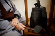 Stan Lombardo, Lawrence, demonstrates how the bell is played during a Morning Bell Chant at the Kansas Zen Center, 1423 N.Y.