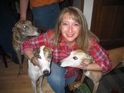 Rhonda Mack, of Lake Zurich, Ill., poses for a photo with recently adopted greyhounds Jack, back left, and Lexi, center, in Lake Zurich, Ill. She adopted the dogs from Dairyland Greyhound Park in Kenosha, Wis., which stopped greyhound racing at the end of 2009. Greyhound advocates are scrambling to find homes for hundreds of dogs that will no longer be racing.