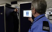 Staff members demonstrate a new full body security scanner Thursday at Manchester Airport in England. European Union countries are not all agreed on whether to use the scanners.