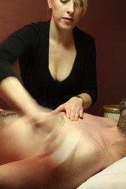 Tara Kuba, esthetician at Salon Di Marco, 733 Mass., performs a chest wax on Gavon Laessig, Lawrence. She applies talc powder first to keep the wax from sticking.