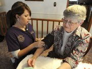 Tyffani Post, a student nurse at Kansas Wesleyan University, takes the blood pressure of Marilyn Ericson in this Dec. 23, 2009, photo in Salina. More than a dozen nurses in Salina have been serving members of a church congregation as a parish nurse.